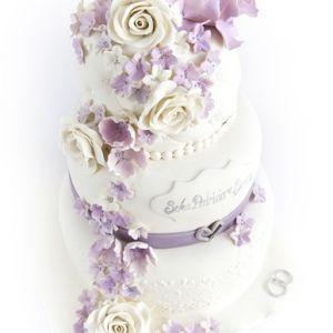 Bryllupskake med romantiske blomster i hvitt og lillatoner