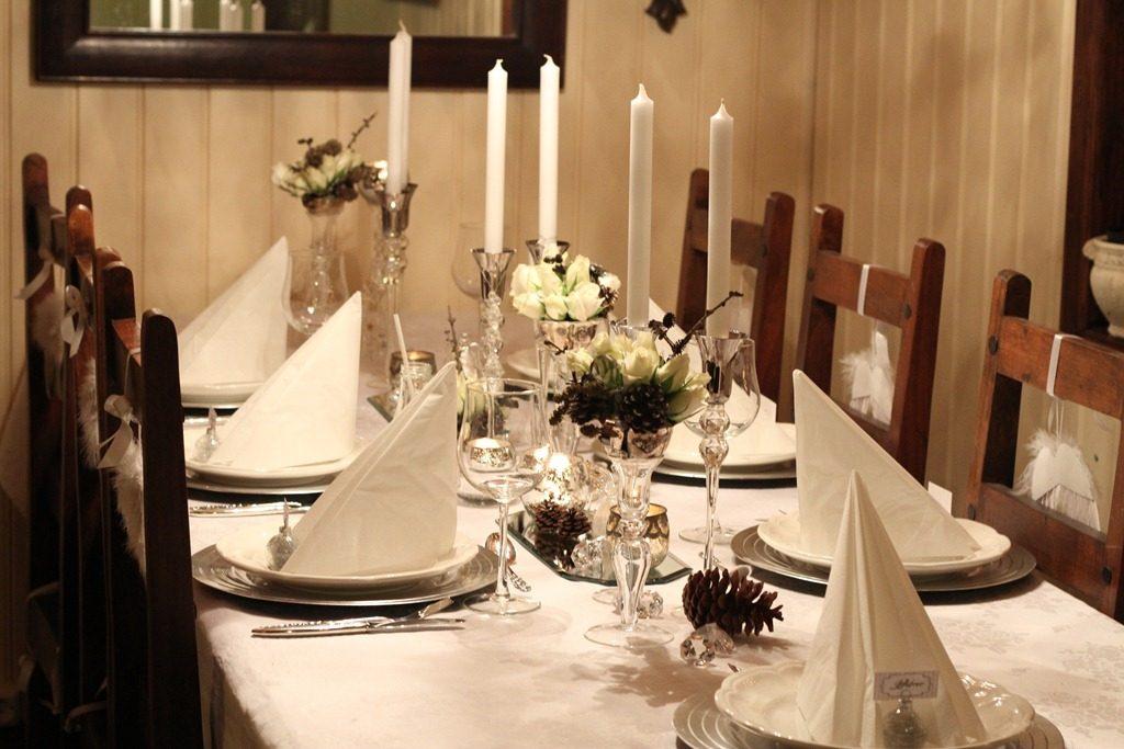 hvitt bord pyntet med sølv, kongler, diamanter og snø